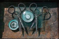 Μεγάλο μαύρο ψαλίδι μετάλλων και παλαιό στρογγυλό ρολόι στη σκουριασμένη επιφάνεια κάτω από το γυαλί, εσωτερικό σχέδιο του τοίχου Στοκ φωτογραφία με δικαίωμα ελεύθερης χρήσης
