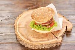 Μεγάλο νόστιμο burger στο στρογγυλό ξύλο Στοκ εικόνες με δικαίωμα ελεύθερης χρήσης