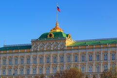 Μεγάλο παλάτι του Κρεμλίνου με τη σημαία της Ρωσικής Ομοσπονδίας στην κινηματογράφηση σε πρώτο πλάνο στεγών σε ένα υπόβαθρο μπλε  Στοκ φωτογραφία με δικαίωμα ελεύθερης χρήσης