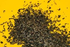 Μεγάλο πράσινο τσάι φύλλων που διασκορπίζεται σε ένα κίτρινο υπόβαθρο E στοκ φωτογραφίες με δικαίωμα ελεύθερης χρήσης
