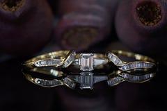 Μεγάλο σμαραγδένιο δαχτυλίδι διαμαντιών περικοπών με το ταίριασμα των ζωνών γάμου και αιωνιότητας Στοκ Φωτογραφία