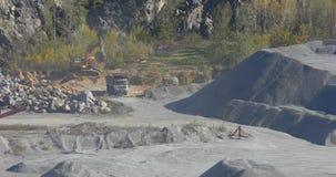 Μεγάλο φορτηγό απορρίψεων σε ένα λατομείο φορτηγών λατομείων, εκσκαφέων και απορρίψεων, βιομηχανικό φορτηγό απορρίψεων σε ένα λατ απόθεμα βίντεο