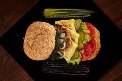 Μεγάλο φρέσκο burger με τη σάλτσα στο μαύρο πιάτο στο ξύλινο υπόβαθρο Στοκ Εικόνες