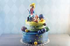 Μεγάλο όμορφο κέικ παιδιών που διακοσμείται υπό μορφή πλανήτη με τα ειδώλια μαστίχας του μικρού πρίγκηπα και της αλεπούς Στοκ Εικόνα
