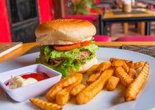 Μεγάλο burger με την πατάτα στο άσπρο πιάτο Juicy burger βόειου κρέατος με τη σαλάτα και ντομάτα με το κέτσαπ Στοκ φωτογραφία με δικαίωμα ελεύθερης χρήσης