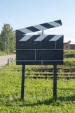 Μεγάλο Clapper κινηματογράφων μεγέθους έννοιας κινηματογράφων σε Ourside στις πράσινες χλόες στο εξωτερικό Στοκ Φωτογραφία