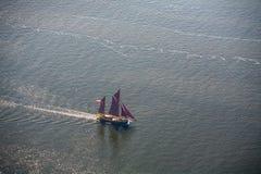 Μεγάλο sailboat πηγαίνει στη θάλασσα κάτω από το πανί επάνω από την όψη Στοκ Εικόνες