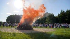 Μεγάλα εγκαύματα φωτιών στο δασικό ξέφωτο, εθνικοί θερινοί εορτασμοί, πλήθος των ανθρώπων γύρω από τη μεγάλη καπνίζοντας πυρκαγιά απόθεμα βίντεο