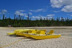Μεγάλα κίτρινα βάρκα και καγιάκ πενταλιών που δένονται στην παραλία Στοκ Φωτογραφία