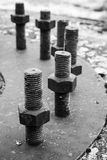 Μεγάλα μαύρα μπουλόνια χάλυβα και καρύδια σε έναν κύκλο Στοκ Εικόνες