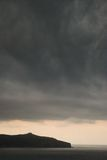 Μεγάλα μαύρα σύννεφα θύελλας πέρα από το έδαφος και τη θάλασσα στοκ εικόνα