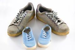 Μεγάλα παπούτσια του πατέρα και μικρά παπούτσια μωρών Στοκ Εικόνες