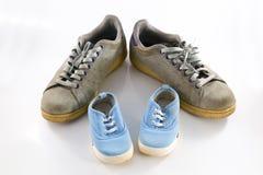 Μεγάλα παπούτσια του πατέρα και μικρά παπούτσια μωρών Στοκ εικόνες με δικαίωμα ελεύθερης χρήσης