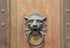 Μεγάλα ρόπτρα πορτών λιονταριών επικεφαλής στο ξύλινο υπόβαθρο πορτών Στοκ Εικόνα