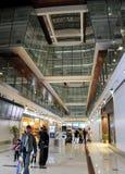 Μεγάλη ελαφριά αίθουσα στον αερολιμένα του Ντουμπάι με τους επιβάτες στη βιασύνη εμιράτα που ενώνονται αρα Σύγχρονο εσωτερικό ύφο Στοκ Εικόνες