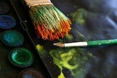 Μεγάλη και μικρή βούρτσα ζωγράφων με τα νερό-χρώματα και το μαύρο έγγραφο Στοκ Φωτογραφία