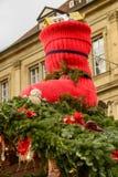 Μεγάλη κόκκινη κάλτσα μεταξύ των κομψών κλάδων στη στέγη στάβλων στο σημάδι Χριστουγέννων Στοκ Εικόνα