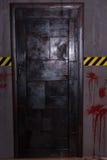 Μεγάλη μαύρη πόρτα σιδήρου κοντά στο κίτρινα και μαύρα σύμβολο και το blo προειδοποίησης Στοκ Φωτογραφία
