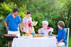 Μεγάλη νέα οικογένεια που ψήνει το κρέας για το μεσημεριανό γεύμα την ηλιόλουστη ημέρα στη σχάρα Στοκ εικόνες με δικαίωμα ελεύθερης χρήσης