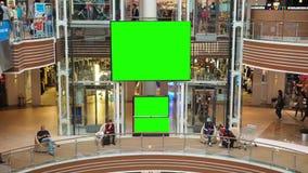 Μεγάλη πράσινη οθόνη στο εμπορικό κέντρο Οι άνθρωποι που περπατούν γύρω και κάθονται πλησίον απόθεμα βίντεο