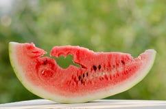 Μεγάλη φέτα του καρπουζιού που κόβεται με ένα σπασμένο βέλος στην καρδιά της σάρκας ενάντια Στοκ εικόνες με δικαίωμα ελεύθερης χρήσης
