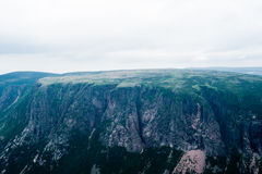 Μεγάλοι απότομοι απότομοι βράχοι και οροπέδιο κάτω από το συννεφιάζω ουρανό και την ομίχλη Στοκ Εικόνες