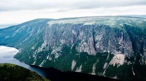 Μεγάλοι απότομοι απότομοι βράχοι και οροπέδιο που διαμορφώνουν το φιορδ κάτω από το συννεφιάζω ουρανό Στοκ φωτογραφίες με δικαίωμα ελεύθερης χρήσης