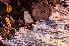Μεγάλοι απότομοι βράχοι στο ηλιοβασίλεμα με την κυματιστή θάλασσα Στοκ εικόνες με δικαίωμα ελεύθερης χρήσης