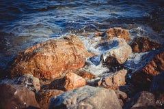 Μεγάλοι υγροί βράχοι, καταβρέχοντας και λάμποντας ήλιος Στοκ Εικόνες