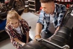 Μεγάλος μπαμπάς και το παιδί του που εξετάζουν τους μηχανισμούς ποδηλάτων Στοκ Εικόνα