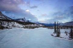 Μεγάλος παγωμένος ποταμός στην κοιλάδα βουνών με τα δέντρα και το δραματικό νεφελώδη ουρανό, εθνικό πάρκο Banff, Καναδάς Στοκ Φωτογραφία