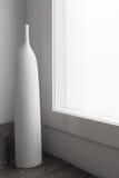 Μεγάλο άσπρο γλυπτό διακοσμήσεων βάζων δίπλα στο μεγάλο παράθυρο Στοκ φωτογραφία με δικαίωμα ελεύθερης χρήσης