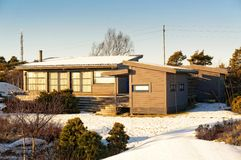 Μεγάλο γκρίζο εξοχικό σπίτι στους βράχους που καλύπτονται με το χιόνι στοκ εικόνες