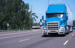 Μεγάλο ημι φορτηγό εγκαταστάσεων γεώτρησης στο μπλε χρώμα με τις μακροχρόνιες δημόσιες σχέσεις ρυμουλκών και καγκέλων Στοκ Εικόνα