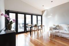 Μεγάλο καθιστικό διαμερισμάτων στούντιο με τις πόρτες πτυχών βισμουθίου Στοκ εικόνα με δικαίωμα ελεύθερης χρήσης