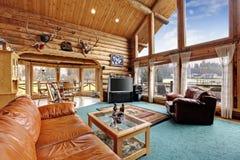 Μεγάλο καθιστικό με η περιοχή στο σπίτι καμπινών κούτσουρων στοκ εικόνα