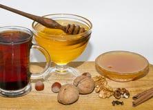 Μεγάλο και μικρό κύπελλο με το σκοτεινά και ελαφριά μέλι, τα φουντούκια και τα ξύλα καρυδιάς και το γυαλί του μαύρου γράμματος Τ  Στοκ φωτογραφίες με δικαίωμα ελεύθερης χρήσης