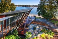 Μεγάλο καλυμμένο μέρος του σπιτιού πολυτέλειας με την άποψη λιμνών Στοκ Εικόνες