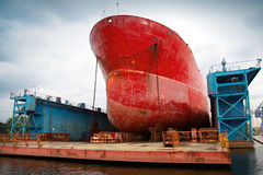 Μεγάλο κόκκινο βυτιοφόρο κάτω από την επισκευή στην επιπλέουσα αποβάθρα Στοκ φωτογραφίες με δικαίωμα ελεύθερης χρήσης