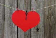 Μεγάλο κόκκινο σημάδι καρδιών με τη βασική ένωση στη σκοινί για άπλωμα από τον παλαιό ξεπερασμένο ξύλινο φράκτη Στοκ φωτογραφία με δικαίωμα ελεύθερης χρήσης