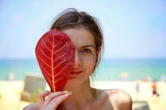 Μεγάλο κόκκινο φύλλο που σκιάζει ένα δεύτερο του όμορφου προσώπου γυναικών Στοκ φωτογραφία με δικαίωμα ελεύθερης χρήσης