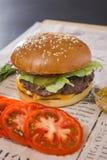 Μεγάλο νόστιμο burger με την τεμαχισμένη ντομάτα σε έναν πίνακα Στοκ εικόνα με δικαίωμα ελεύθερης χρήσης