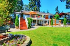 Μεγάλο πορτοκαλί σπίτι με την άσπρη περιποίηση Άποψη της πίσω αυλής με την περιοχή patio στοκ εικόνες