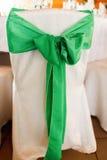 Μεγάλο πράσινο τόξο που ντύνεται σε μια άσπρη καρέκλα Στοκ φωτογραφία με δικαίωμα ελεύθερης χρήσης