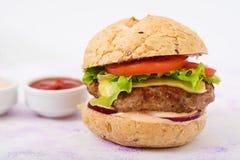 Μεγάλο σάντουιτς - χάμπουργκερ με juicy burger βόειου κρέατος, το τυρί, την ντομάτα, και το κόκκινο κρεμμύδι Στοκ Φωτογραφία