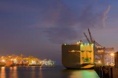 Μεγάλο σκάφος με το λειτουργούντα γερανό στη λιμενική νύχτα Στοκ Εικόνα