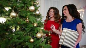 Μεγάλο χριστουγεννιάτικο δέντρο με τις χρυσές σφαίρες και τις ακτινοβολώντας γιρλάντες, φίλη κοντά στο χριστουγεννιάτικο δέντρο,  απόθεμα βίντεο