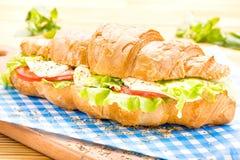 Μεγάλο croissant σάντουιτς με το μπέϊκον, μαρούλι, ντομάτα, τυρί Στοκ Εικόνες