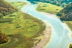 Μεγαλοπρεπές τοπίο του Μαυροβουνίου - ποταμός Crnojevica που κάμπτει στο εθνικό πάρκο λιμνών Skadar Στοκ Εικόνα