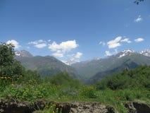 Μεγαλοπρεπή καυκάσια βουνά και φωτεινός μπλε ουρανός Στοκ Εικόνα